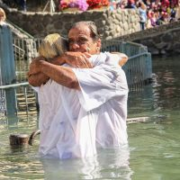 Hugs and emotion during baptism River Jordan