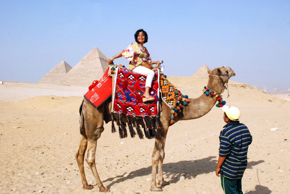 Enjoying a camel ride in front of the pyramids